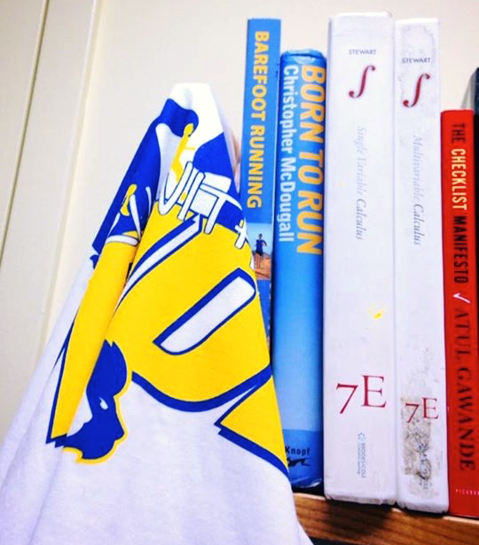 The books Born To Run, Barefoot Running, and James Stewart's Calculus on a shelf
